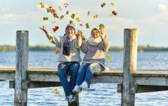 Seniorenpaar wirft buntes Laub in die Luft, Herbsttag am See